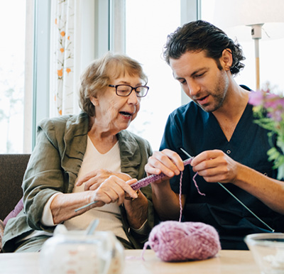 Senior woman and male caregiver discussing knitting techniques at a table