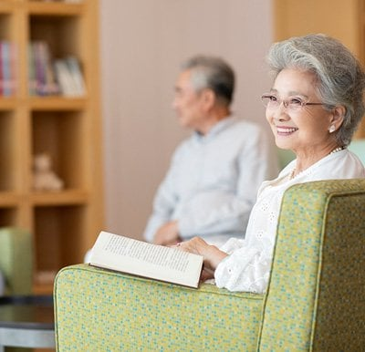 Woman in library smiling in a green lounge chair.