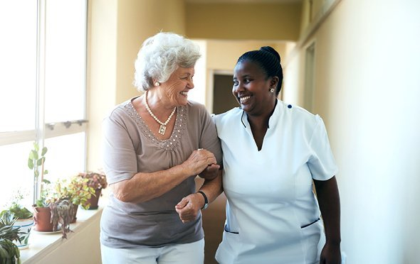 Smiling caregiver assisting a resident down a hall with large window and potted plants.
