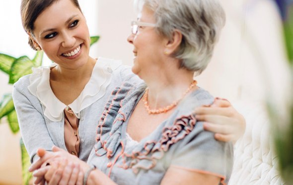 Smiling caregiver sitting with her arm around a resident and holding hands.