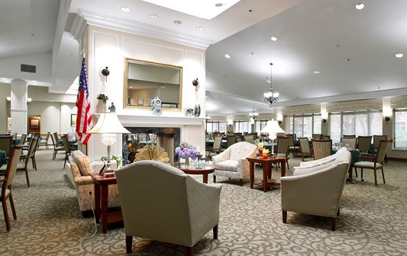 Large, elegant dining room with multiple tables, a fireplace in the center and lounge seating at Olde Raleigh assisted living community in Raleigh, NC.