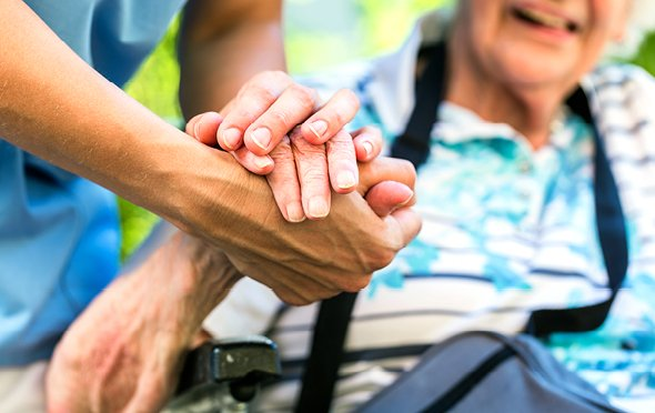 Close up of a caregiver and resident's held hands.