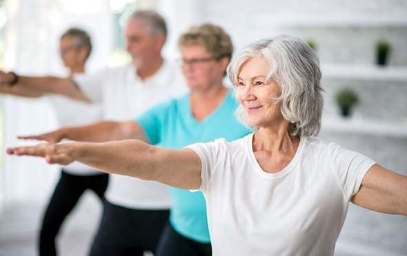 Senior woman holding a yoga pose in a yoga class with other seniors
