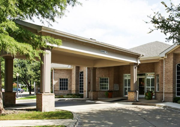 The front entrance of an assisted living community in Richardson Texas, with a portico, large trees and potted plants.