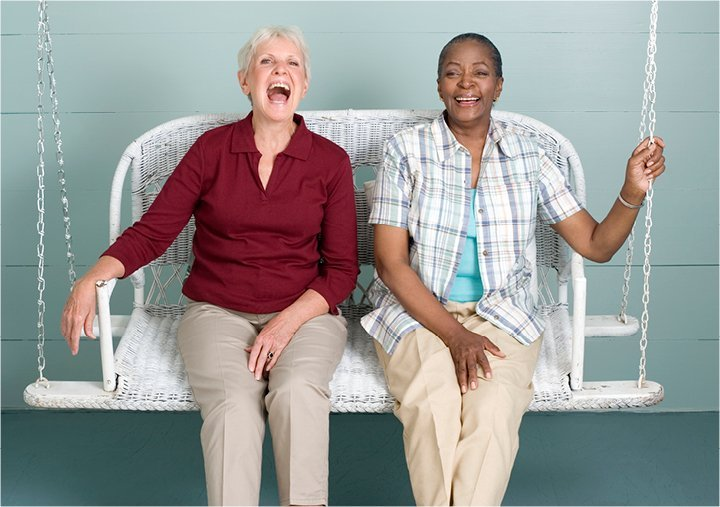 Two women laughing and swinging together on a porch swing