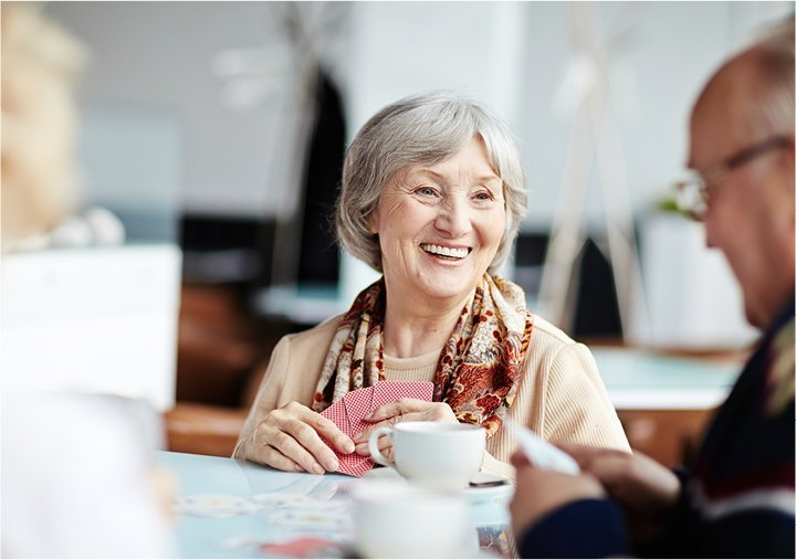 Senior woman smiling and enjoying coffee with friends at a table