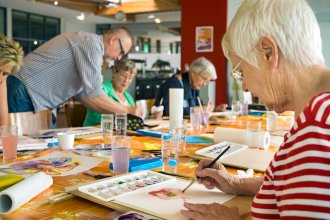 Group of seniors paint with help of instructor as a form of therapy