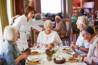 A table of seniors enjoying a meal in a senior living facility dining room.