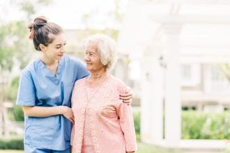 Young caregiver woman embraces senior woman while on a walk.