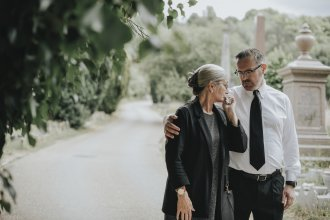 Senior woman dressed in black is embraced by younger man after a funeral.
