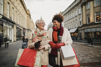 Women enjoy shopping for holiday gifts in a downtown setting.