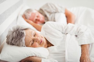 Senior couple sleeping in a bed.