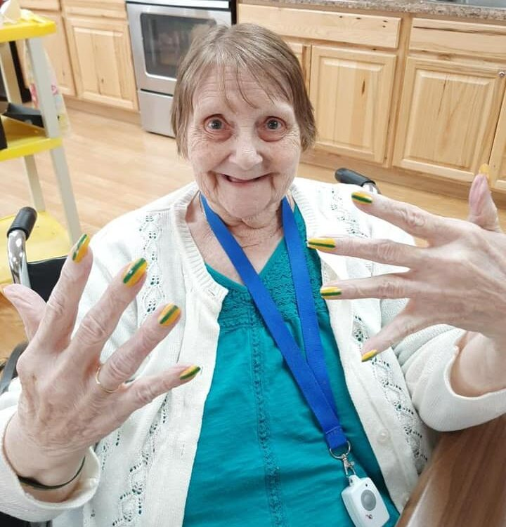 senior woman smiles with painted nails at the waterford at west bend, a senior community in wisconsin