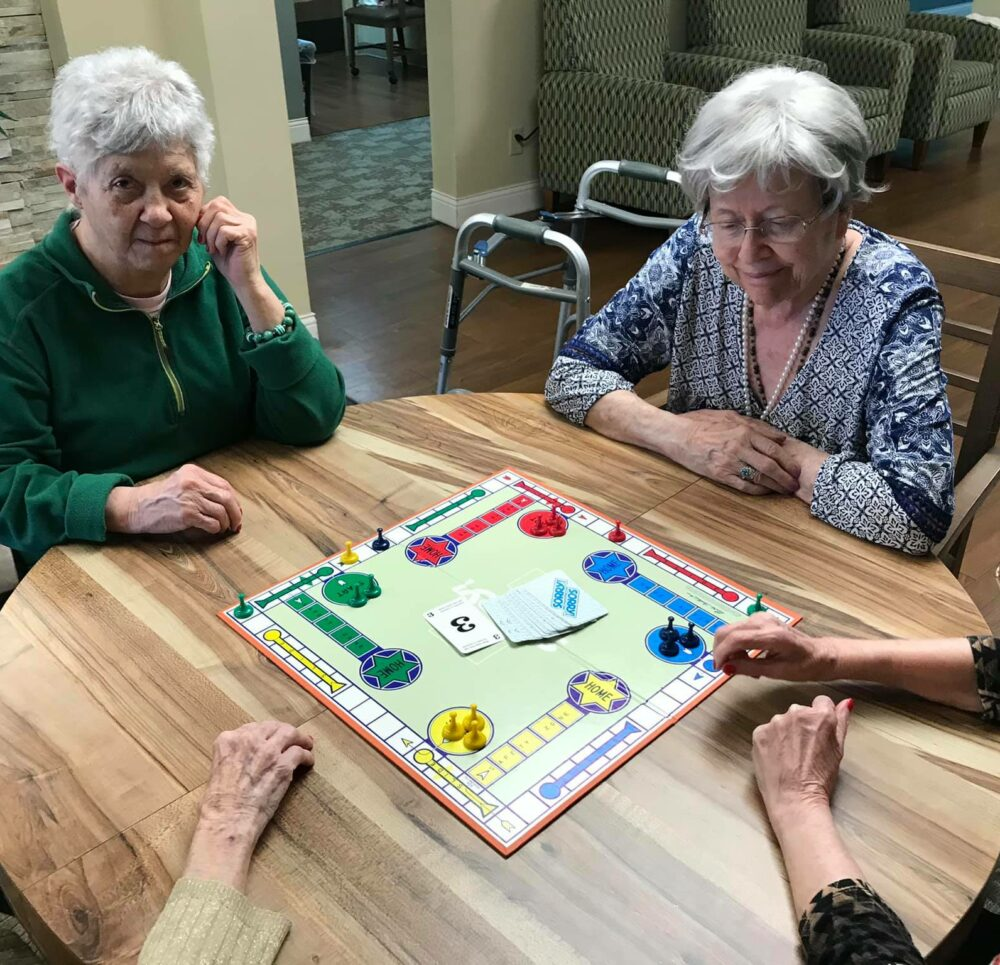 group of senior women play a board game at crown pointe, a senior community in omaha, nebraska