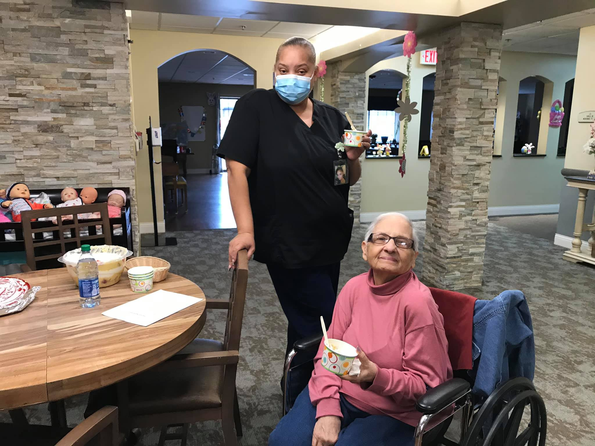 senior woman and woman caregiver smile together at crown pointe, a senior community in omaha, nebraska
