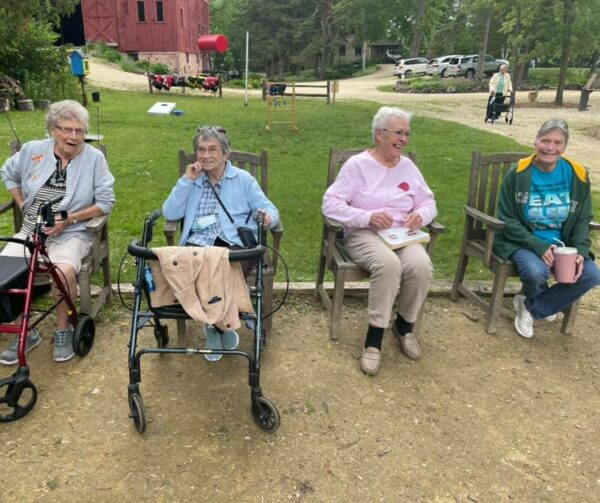 Four senior women sitting outside at a senior living community in West Bend, Wisconsin.