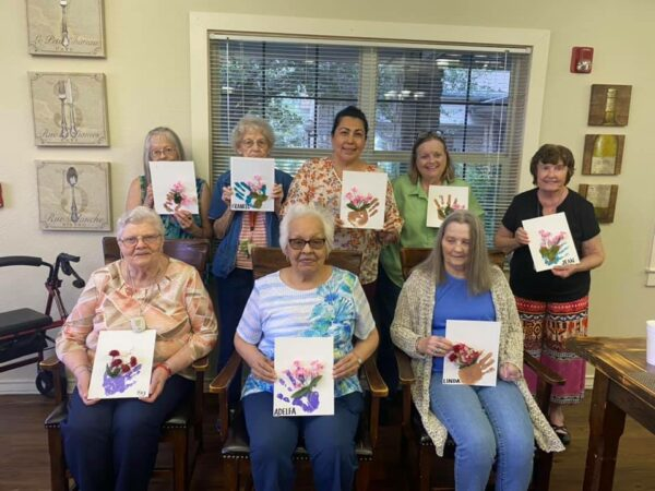 Eight women take a group shot together holding up their artwork at a senior living community in Stephenville, Texas.