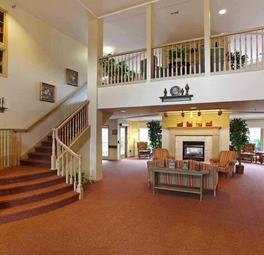 Two-story lobby with fireplace and seating at a senior living facility in Lincoln, Nebraska.