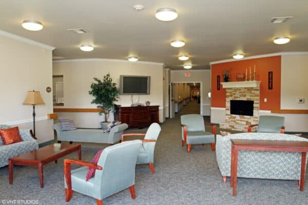 Lobby with seating and a fireplace at the Courtyards at Lake Granbury, a senior living community in Granbury, Texas.