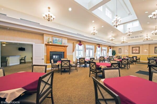 Dining room at a senior living community in Dayton, Ohio with ample natural light, plenty of seating and a fireplace.