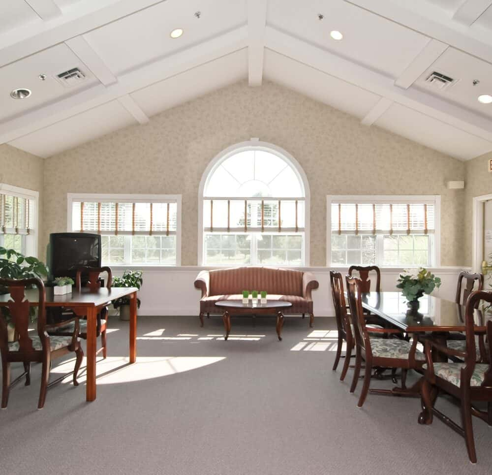 whispering pines senior living community living room area with large windows