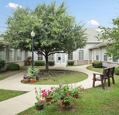 Courtyard at a senior living community with a paved walking path, bench, landscaping and potted plants.