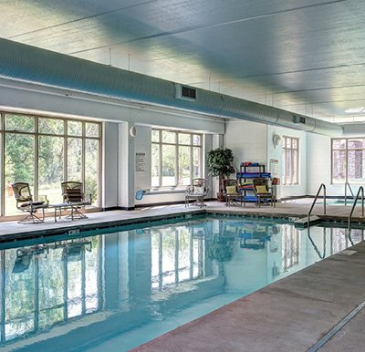 Window-lined indoor aquatic center pool and whirlpool at an independent living community in Green Bay, Wisconsin.