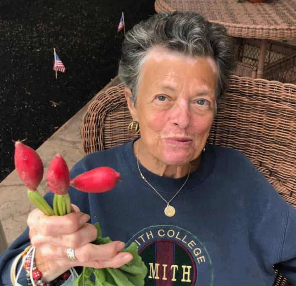 A smiling woman holding three red tulips and enjoying a beautiful day outside in a wicker chair.