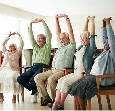A group of seniors stretching their arms overhead during a chair yoga class.