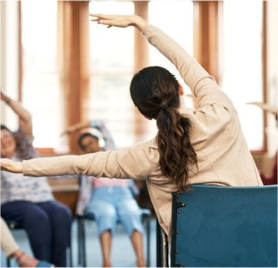 Caregiver leading seniors in a chair yoga stretching exercise.
