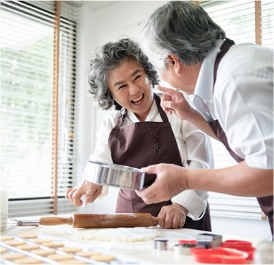 Senior man and woman laughing while making cookies.