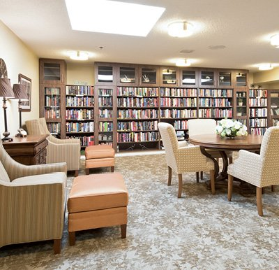 Beautiful library in senior living facility with built-in wood shelving and cabinetry along the back wall, comfortable arm chairs and a table in the center of the room in Omaha, Nebraska.