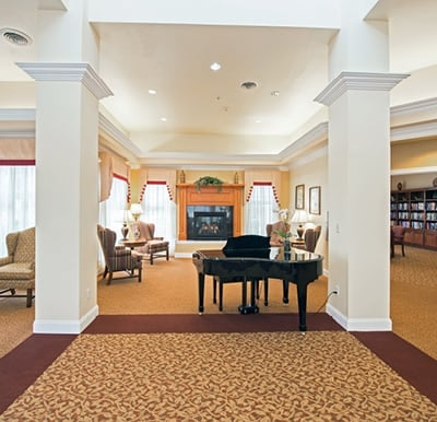 Grand space with columns, a grand piano, a fireplace, lounge seating and French doors opening to a well-stocked library in Dayton, Ohio.
