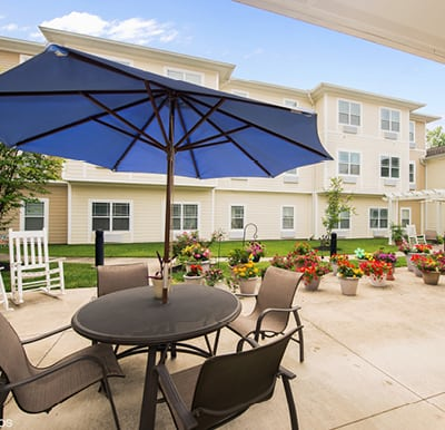Large patio in courtyard with umbrella covered tables and a walking path in Dayton, Ohio.