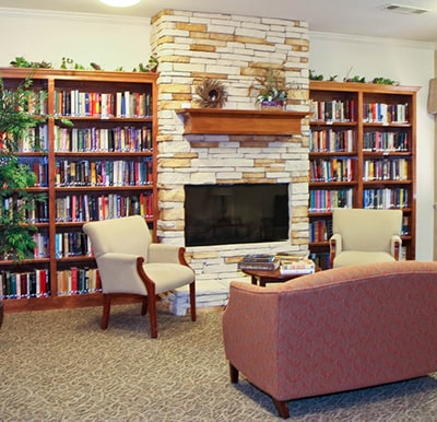 A fireplace with bookshelves surrounding it and comfortable lounge seating.