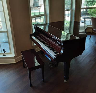 Grand piano in a lounge area with large windows.