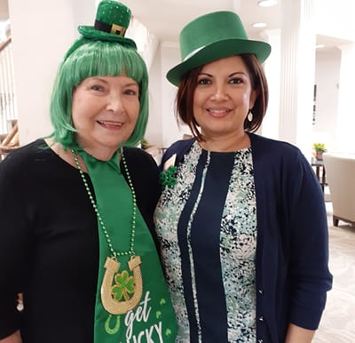 A senior living resident with a staff member wearing St. Patrick's day outfits in San Antonio, Texas.
