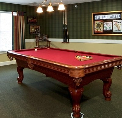 A billiards table in a large activity room with chandelier overhead.