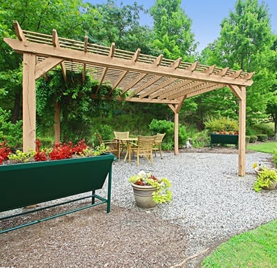A pergola and raised gardens in a well-landscaped courtyard.