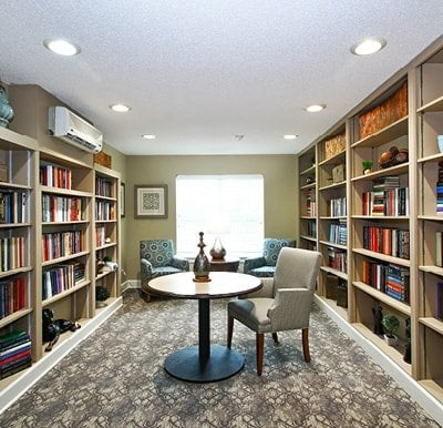Well-stocked library with bookshelves covering two walls and tables with chairs in the center of the room.