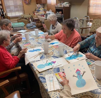 A group of senior women enjoying a craft in the activity room.