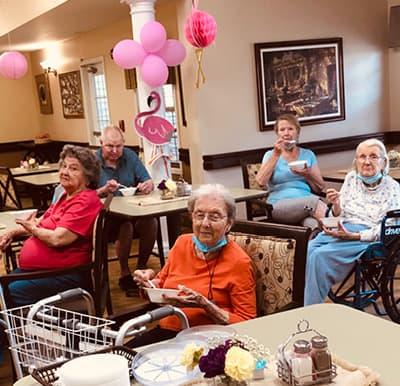 A group of seniors enjoying food at a themed party.