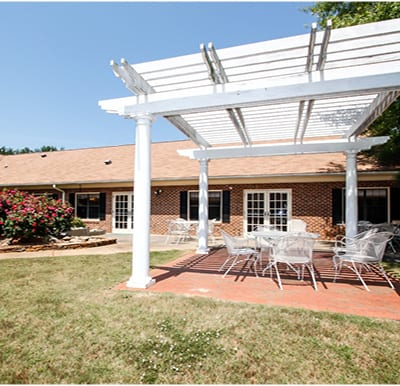 A beautiful, white pergola with outdoor dining furniture in a well-manicured courtyard.