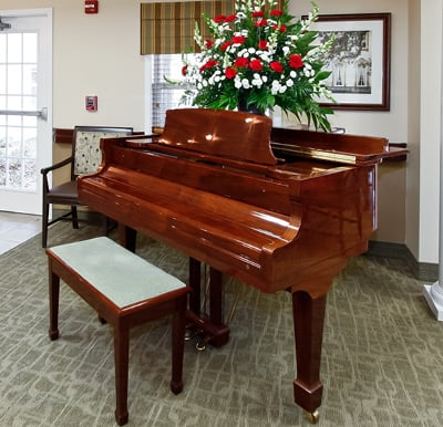 A grand piano with a large bouquet of roses on top.