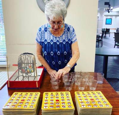 Woman setting up a game of bingo in the activity center in Raleigh, North Carolina.