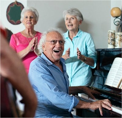 Senior man playing piano with friends gathered and clapping.
