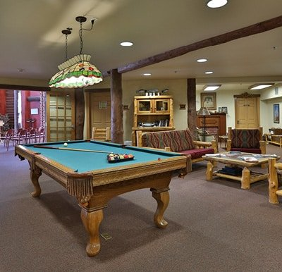 A spacious and open activity center with a billiards table and lounge area.