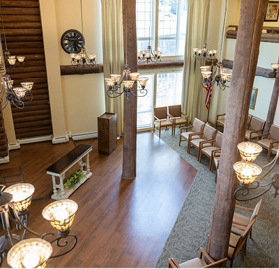 Senior living community room with floor to ceiling windows, plenty of seating, a piano and dance floor and elevated stage area in the corner