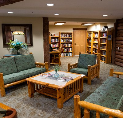 Library room in loft area of senior living community with a log-cabin style table and chairs and wooden bookcases