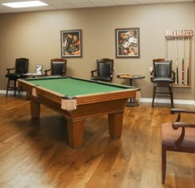 A billiards table in a large room with many chairs.